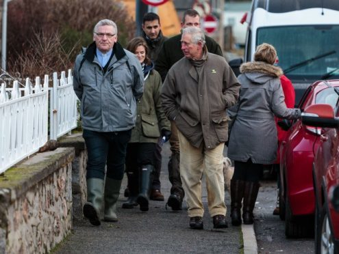 Prince Charles speaks to residents in Ballater earlier this year amongst the devastation in the wake of Storm Frank