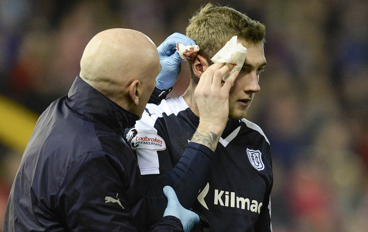 Dundee's Kevin Holt receives treatment after he was caught by a high Shay Logan boot