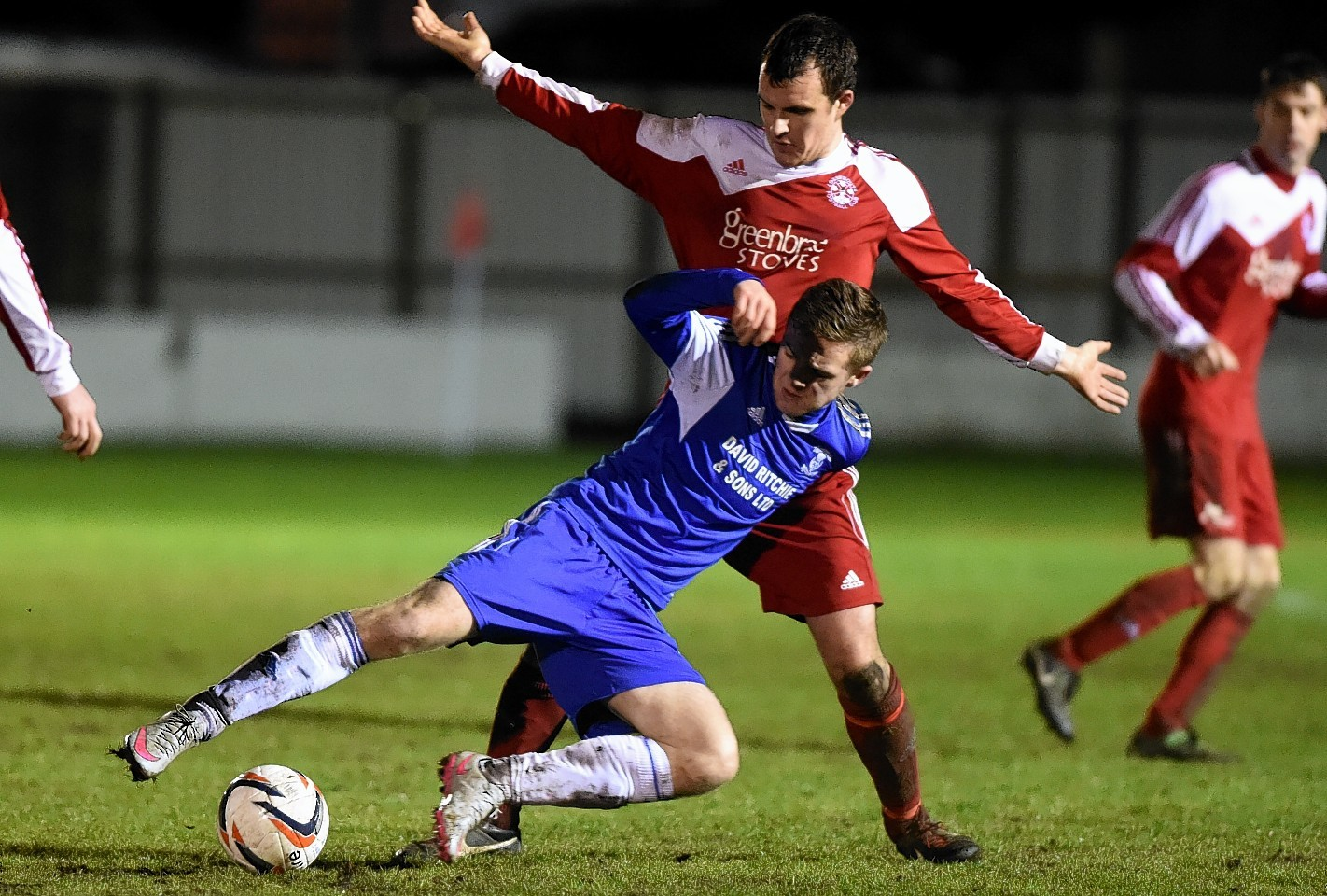 Strathspey Thistle's Josh Peters challenges Lossiemouth's Mark Hector challenge for the ball.
