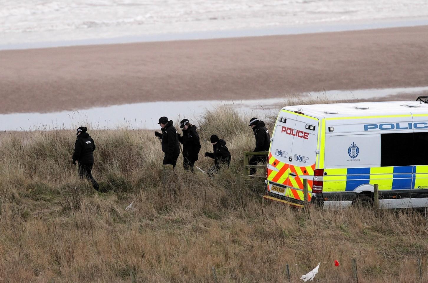 Police search the beach at Lunan Bay