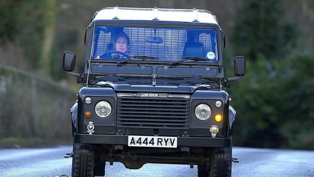 The Queen driving herself in a Land Rover Defender.
