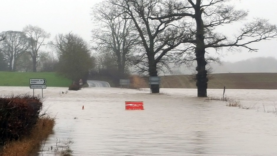 The closed A923 Blairgowrie to Coupar Angus road in Perthshire as communities were warned that more heavy rain across the UK could lead to further flooding