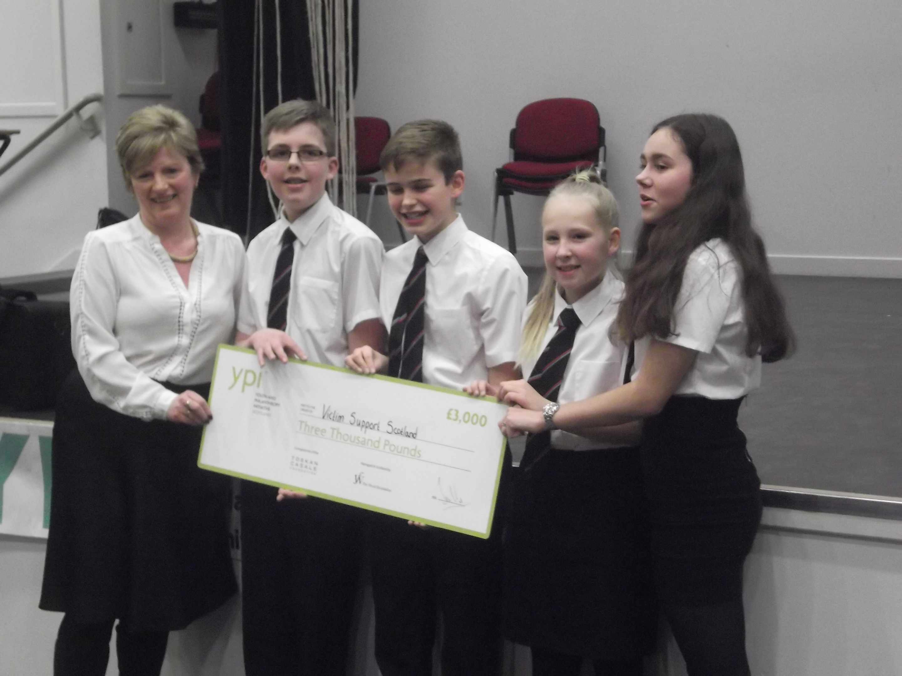 Caption: Portlethen Academy pupils Keir McKechnie, Taylor Lumsden, Calum Graham and Alyssa Hay being handed the cheque for £3,000 for Victim Support Scotland.