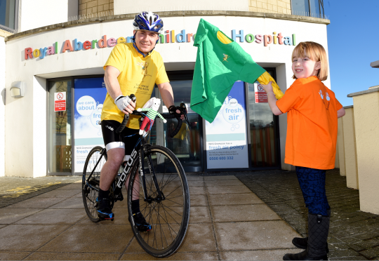 Green for go! Stella Shiner, a patient at Aberdeen Children's Hospital, waves off cyclist Nick Frost who is going to cycle 10,000km round Scotland in aid of the ARCHIE Foundation.