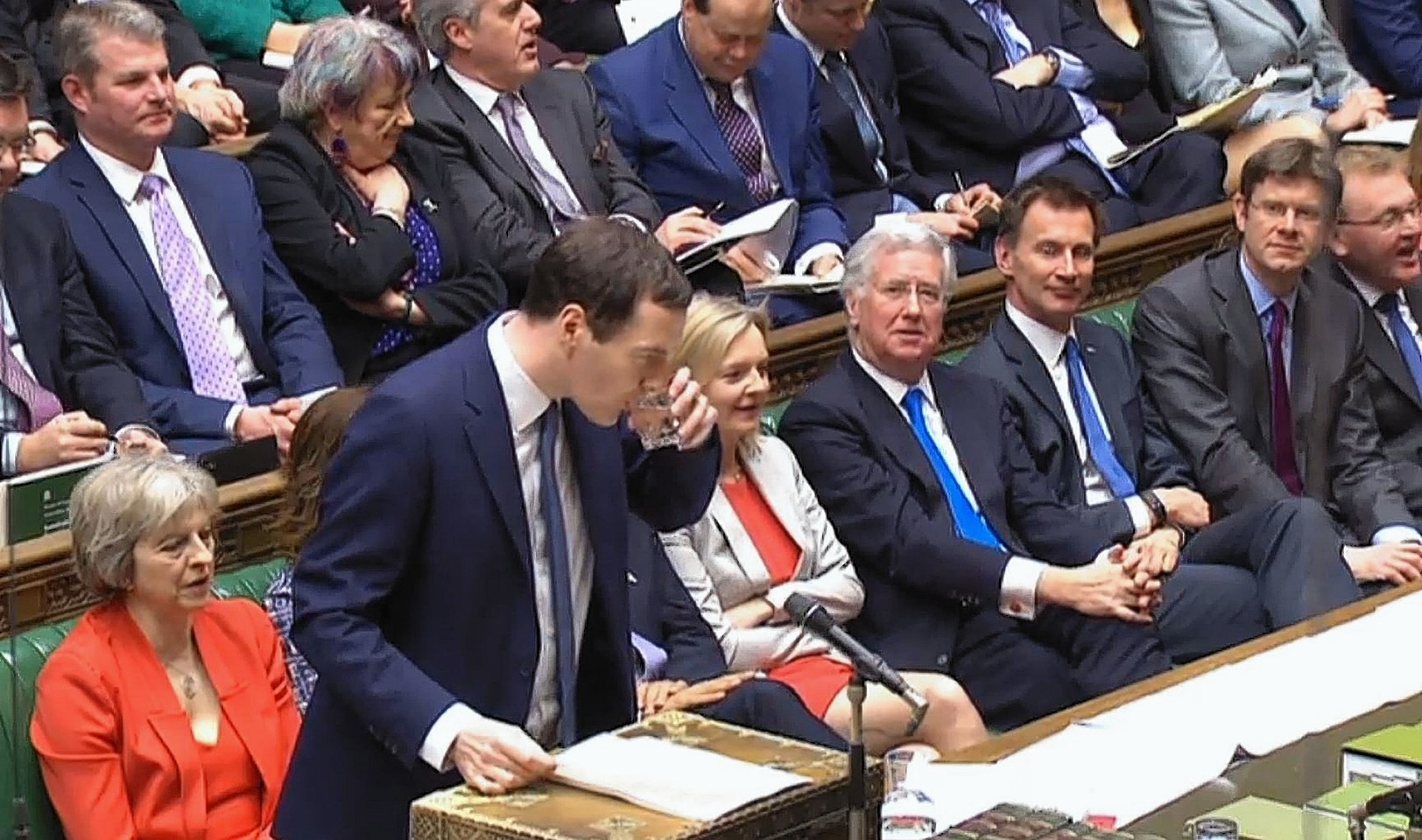 Chancellor of the Exchequer George Osborne pauses for a drink as he delivers his Budget statement to the House of Commons
