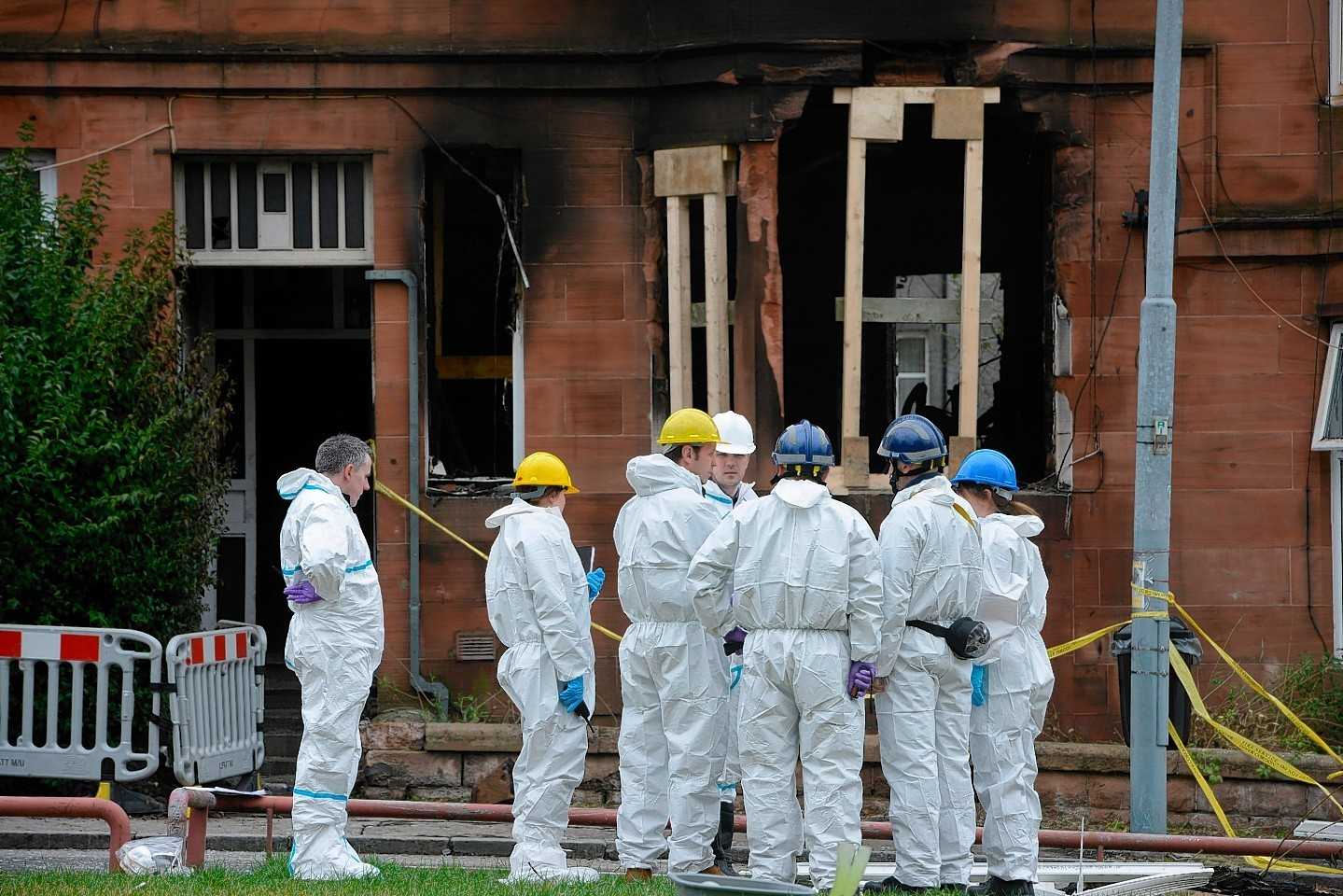 Forensic teams inspects the scene of the blaze