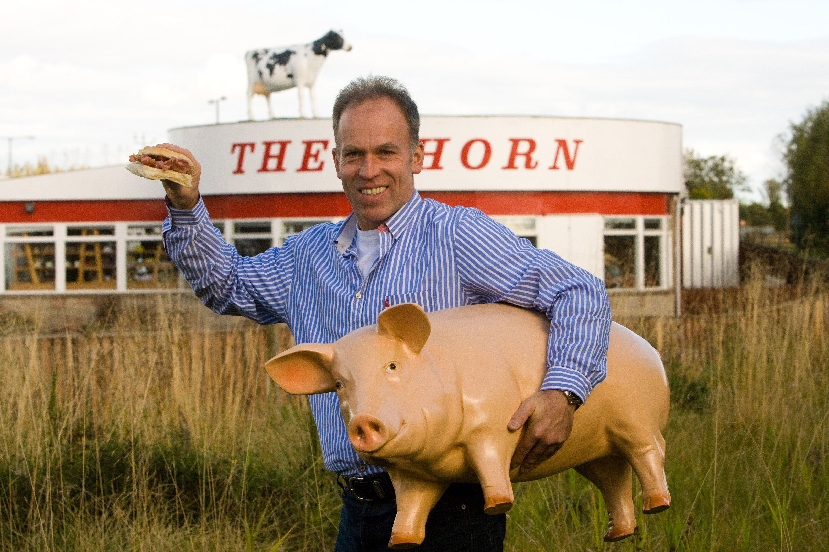 The Horn, A90 by Errol. Best Bacon Buttie in the World. The cafe was voted Best Bacon Buttie by website users. Pictured, owner Kenny Farquharson holding a prop pig he made (along with the famous cow on top of the building).