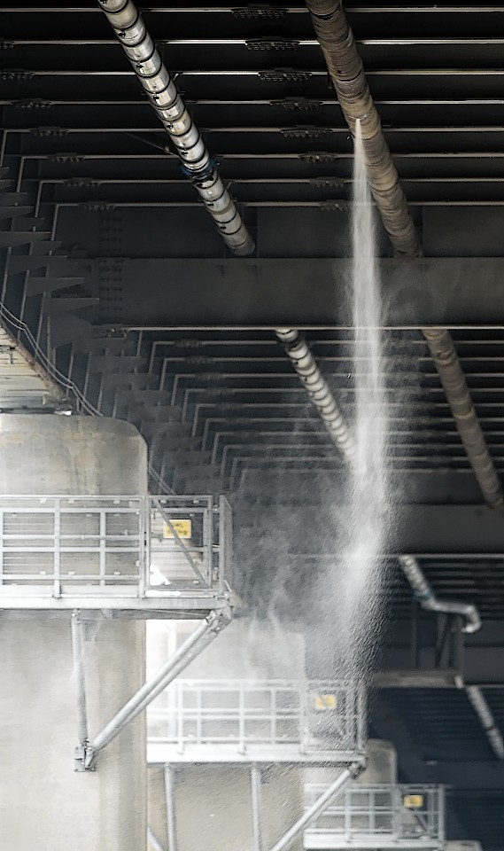 Water pours under pressure from a water pipe beneath the Kessock Bridge