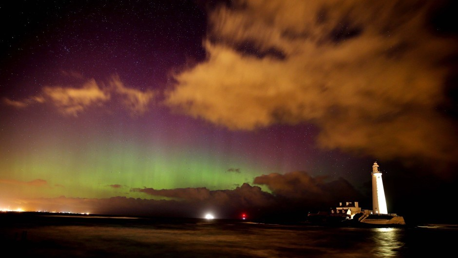The Northern Lights shine over St Mary's Lighthouse near Whitley Bay in Northumberland
