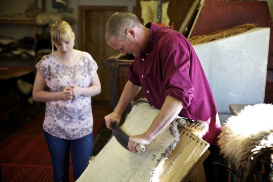 Pete Winterbourne, Skyeskyns tanner demonstrates the fleshing beam to trainee tanner, Roma MacRae.