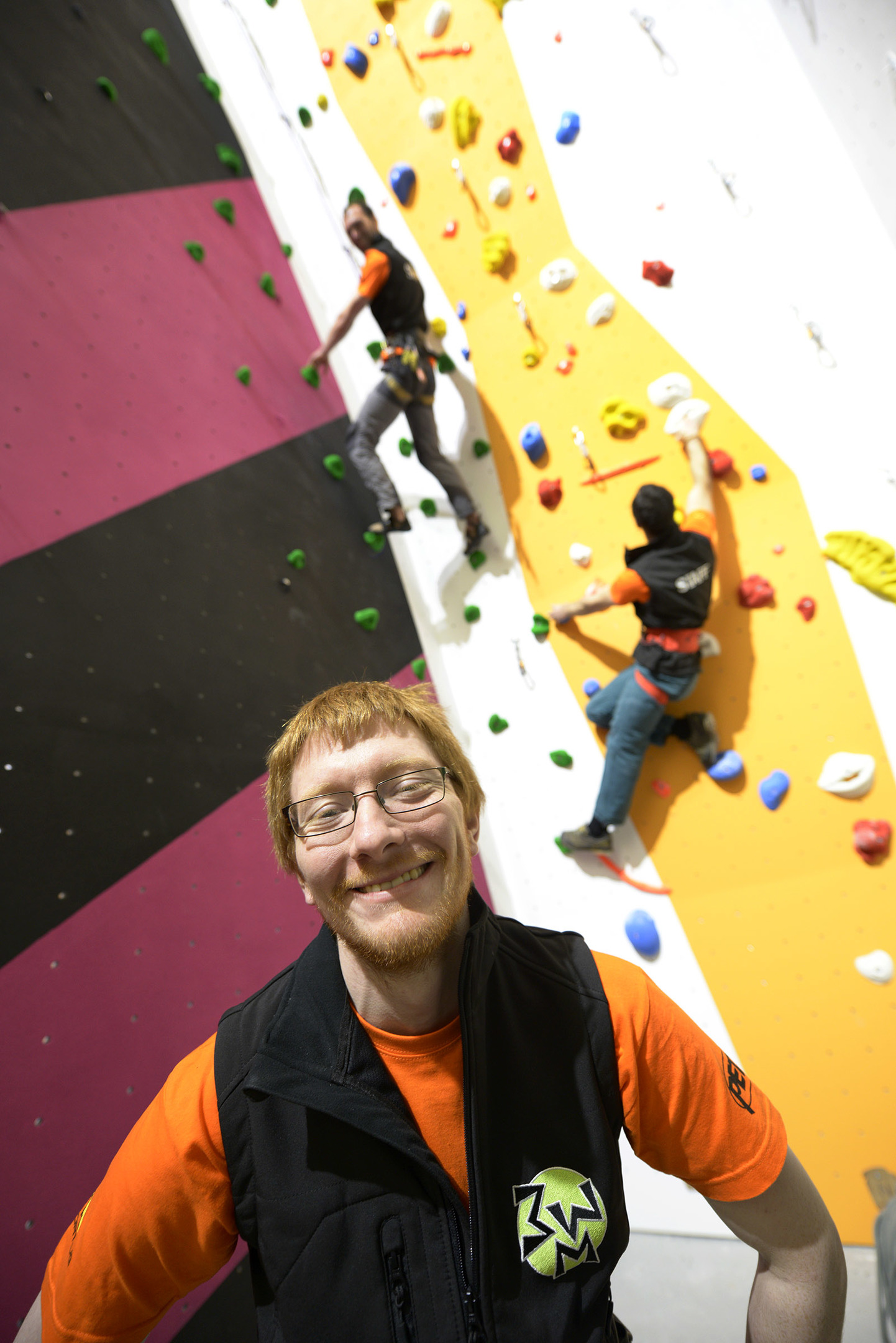 Oliver Millington surrounded by the colourful climbing walls of Three Wise Monkeys Climbing, which opens in May