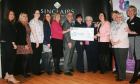 Staff and volunteers from CLAN Cancer Support receive a donation from the Sinclair family