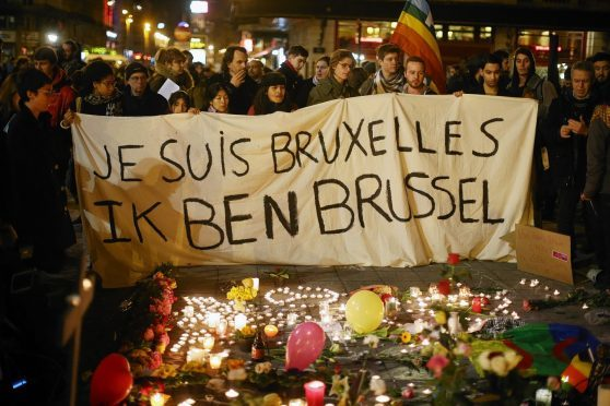 People hold up a banner as a mark of solidarity at the Place de la Bourse