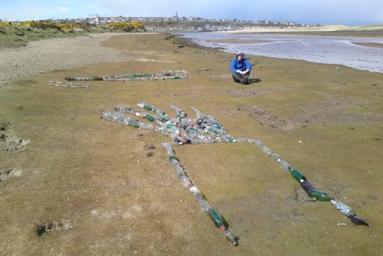 Pete Miner used almost 400 bottles to create the display to highlight litter on the Lossiemouth coast.