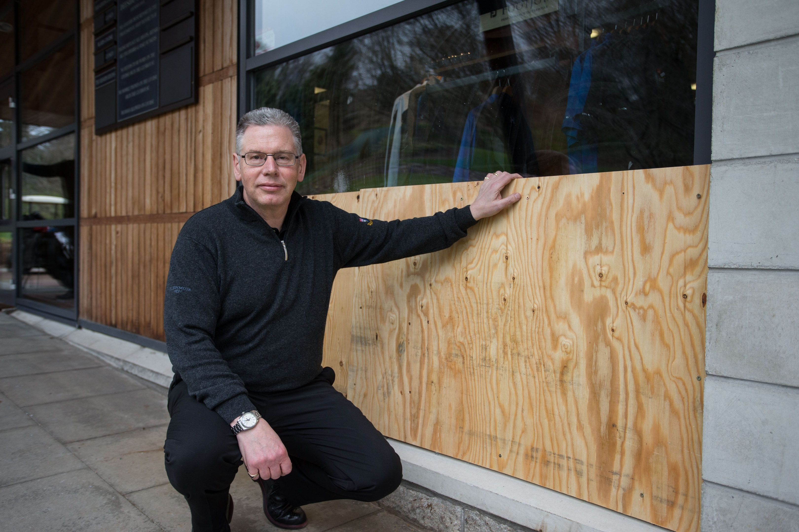 Professional Frank Coutts sits by the smashed window