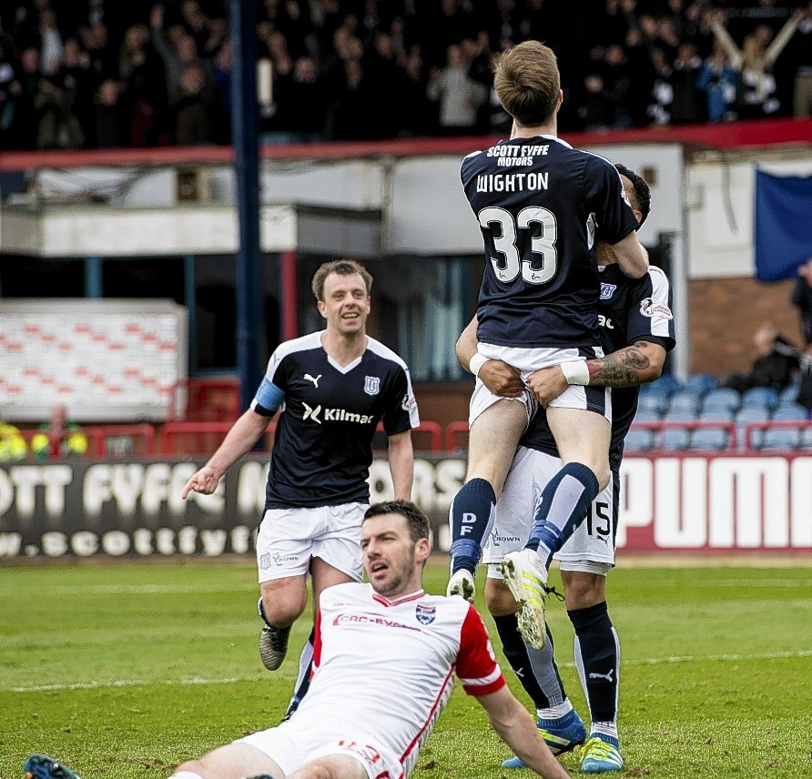 Craig Wighton celebrates after scoring Dundee's fourth goal beside a dejected Paul Quinn