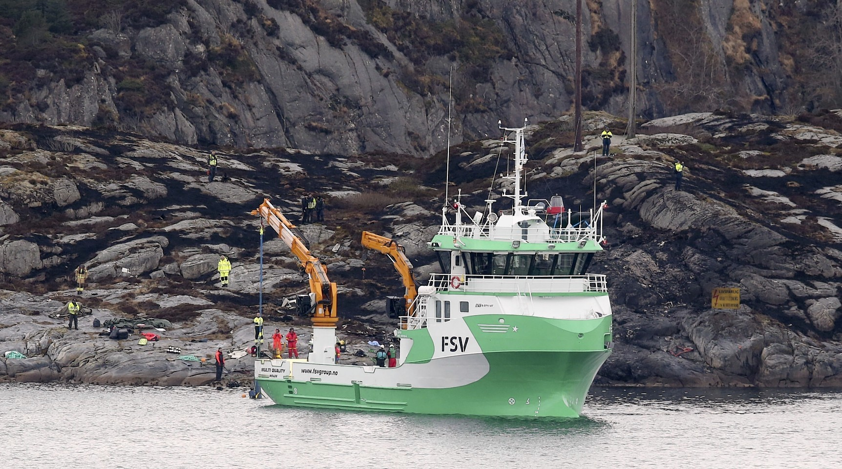 A recovery vessel lifts parts of the crashed helicopter