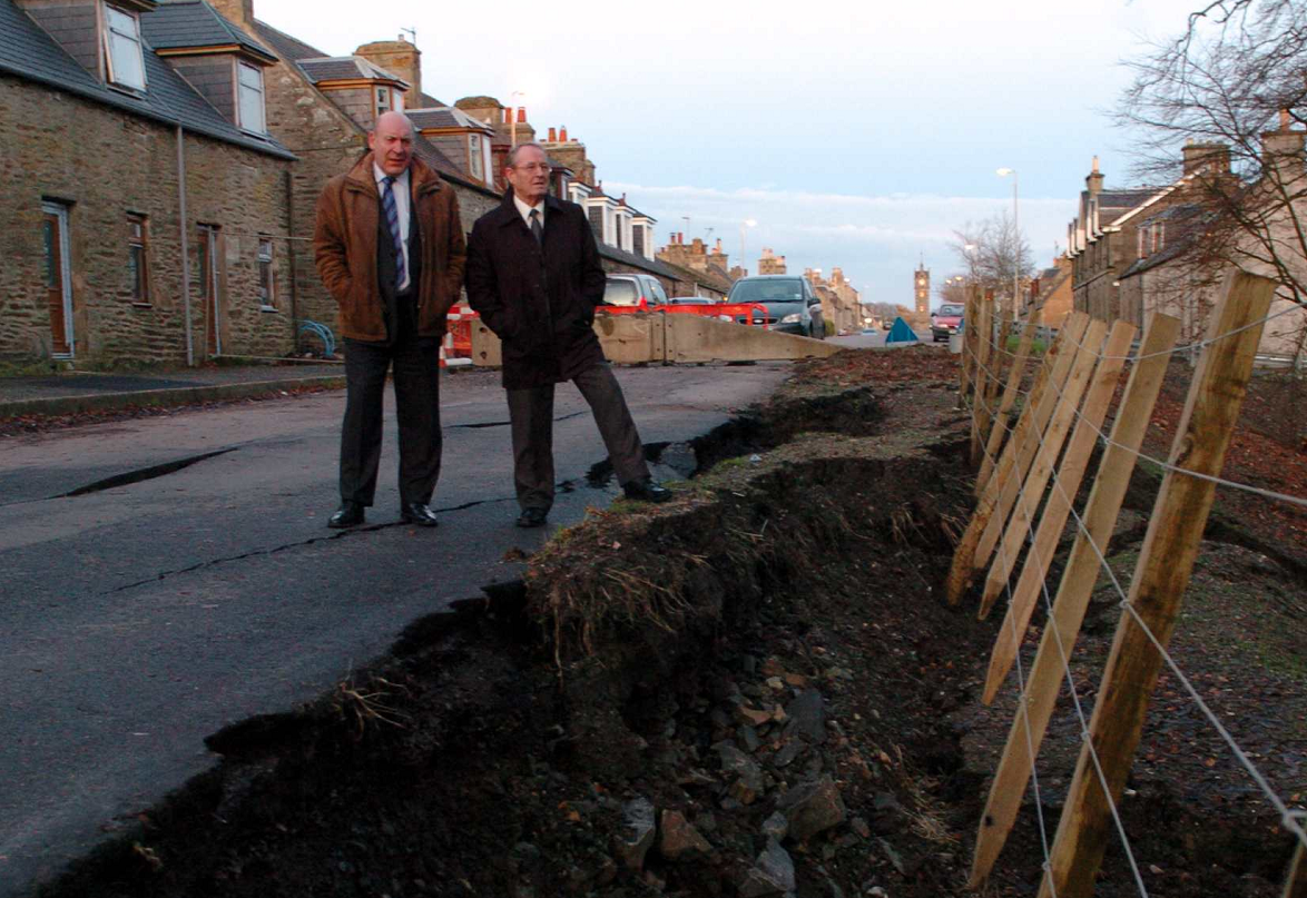 Moray councillors, Stewart Cree, left, and Ron Shepherd, right, by the flood damaged road in Newmill in 2009.