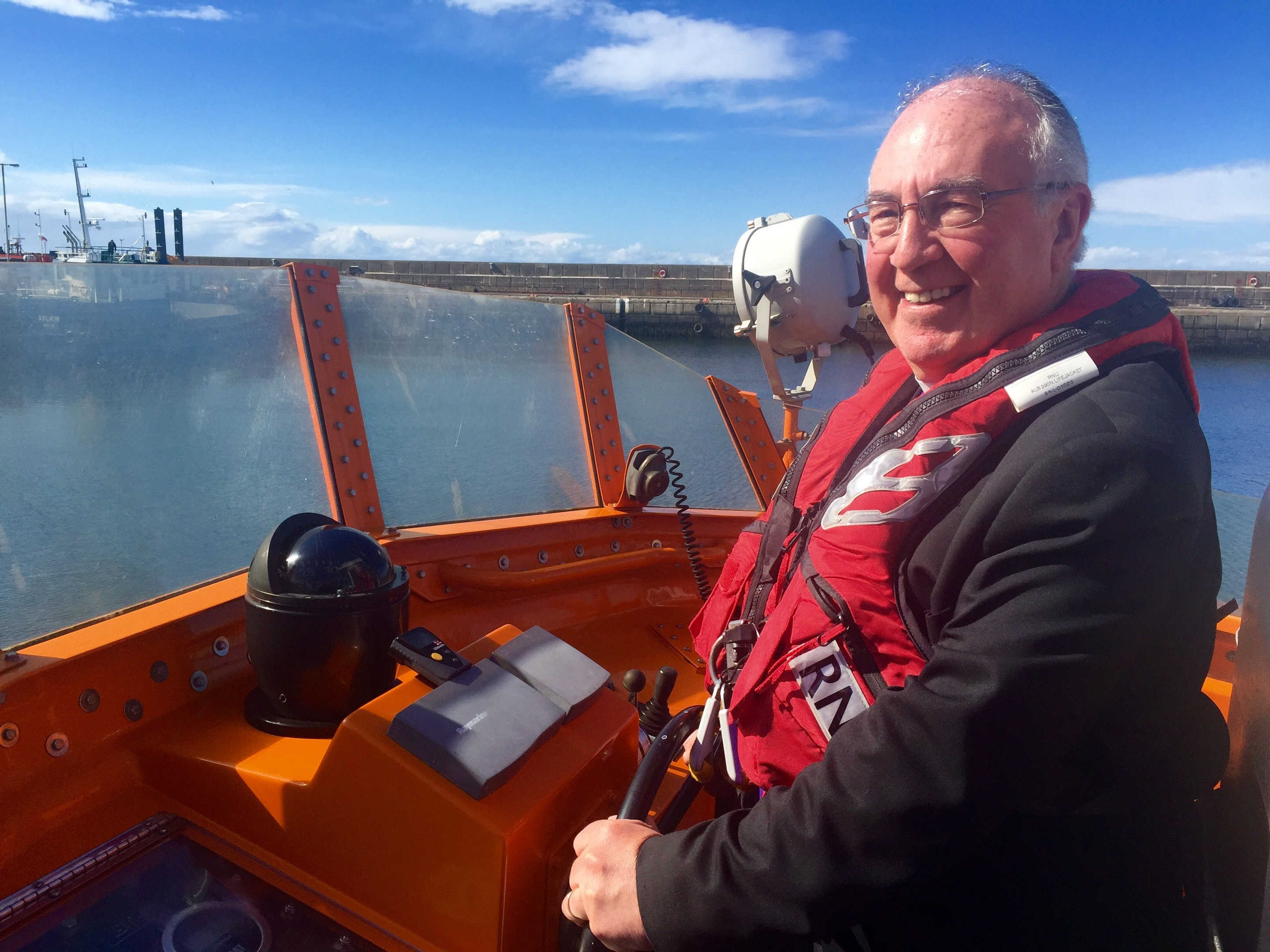 Church of Scotland moderator Rt Rev Dr Angus Morrison at the helm of the lifeboat in Buckie.