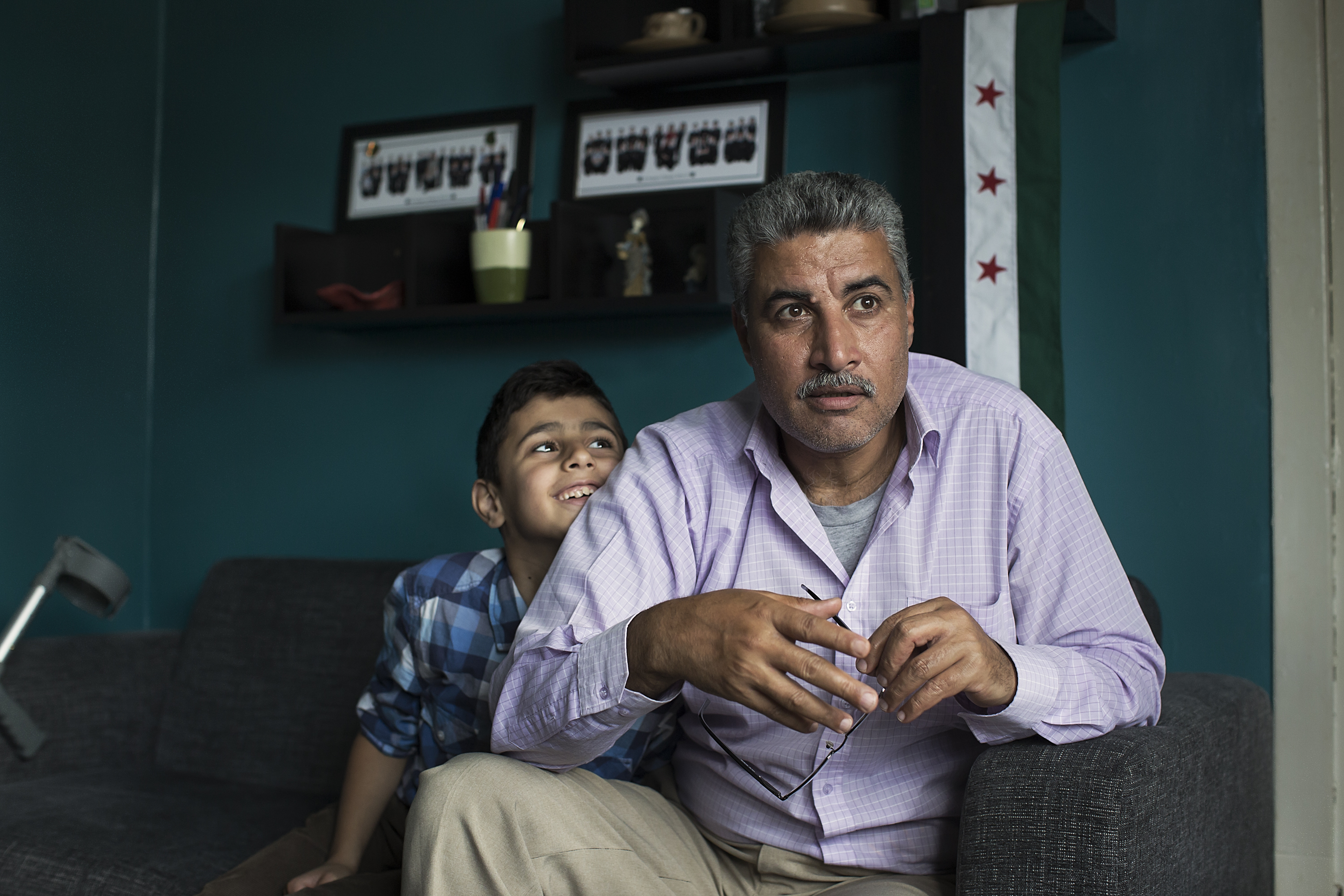 Thamer Al-Johmani sits at home as his youngest son Omar cuddles his father.