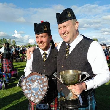 Lead Drummer Cameron McClure and Pipe Major Scott Taylor, of the City of Inverness Pipe Band collect their trophies