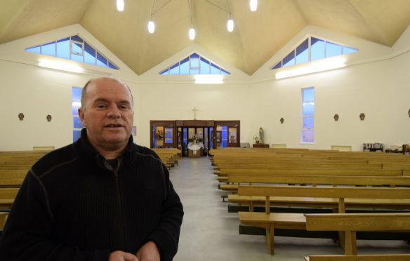 Father Roddy McAuley in the church where the new window will be installed above the door