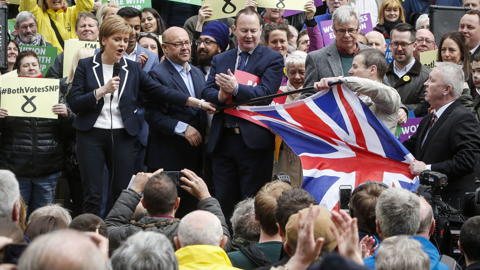 SNP leader Nicola Sturgeon holds a pole attached to a union flag after a man brought it to an SNP campaign event on Buchanan Street in Glasgow