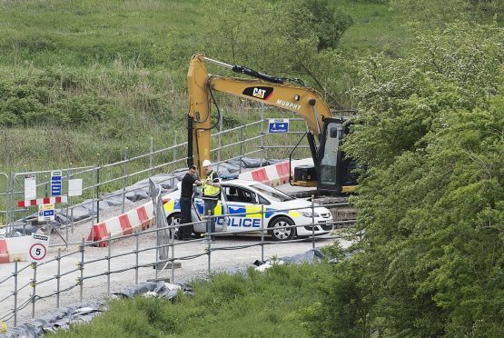 Police search for the remains of a body at Block Fen Quarry where a severed head was discovered on Monday.