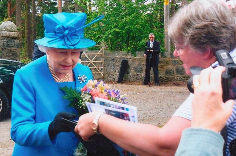 Sheila Clark shows the Queen some of her photos