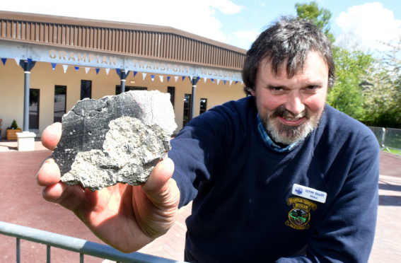 Curator Mike Ward with a piece of the Berlin Wall at the Grampian Transport Museum, Alford.