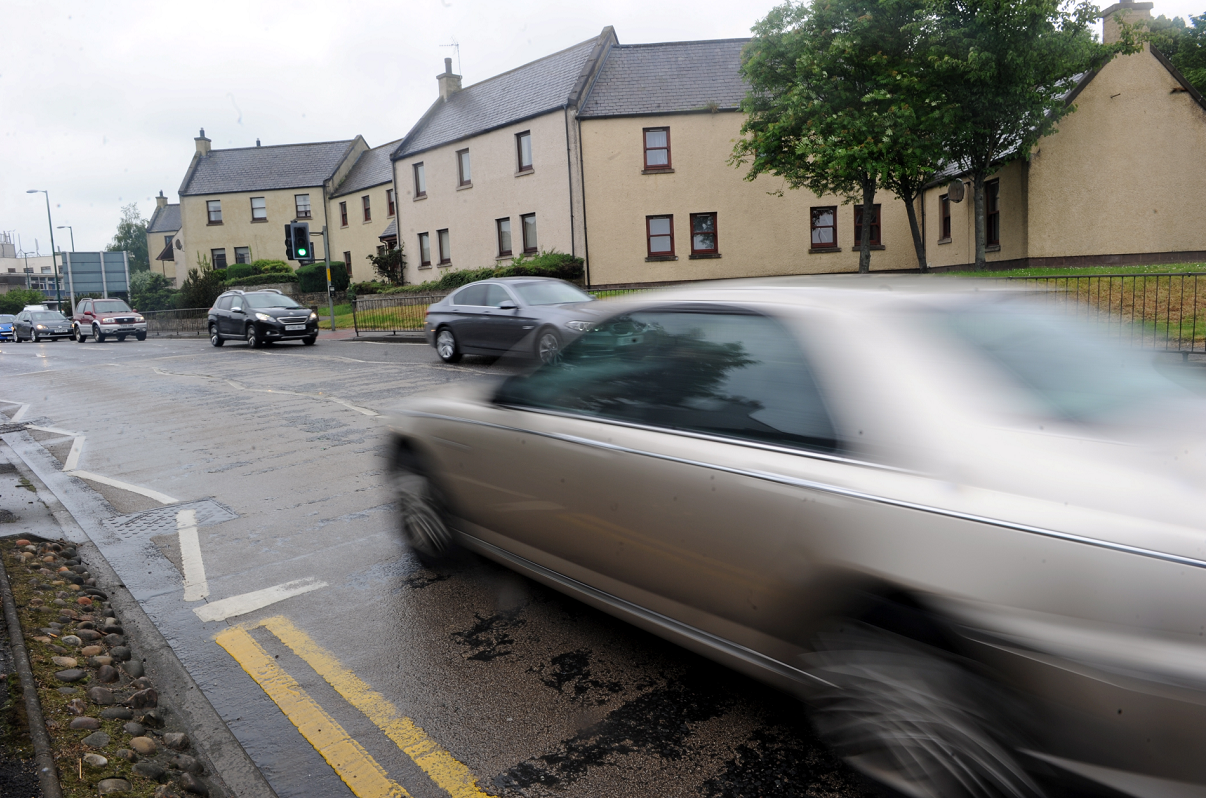 Cars on Alexandra Road, Elgin, going past the back of houses on Murdoch's Wynd. Picture by Gordon Lennox