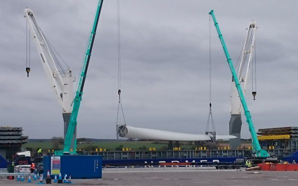 Two cranes working in tandem to lift the turbine blades onto special trailers at the Port of Cromarty Firth