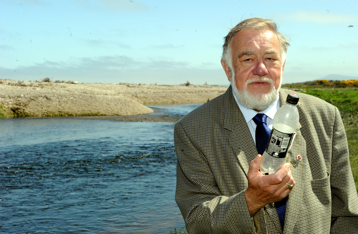 James Mackie, chairman of the James A. Mackie Trust beside the Spey Estuary at Kingston, with a plastic bottle washed ashore. Picture by Gordon Lennox.
