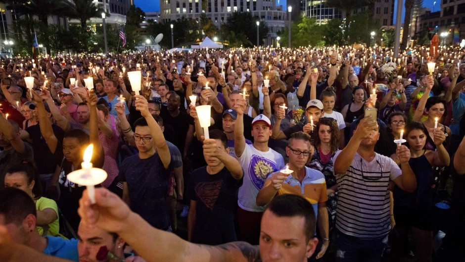 Crowd members hold up candles during a vigil in Orlando for the victims of the mass shooting (AP)