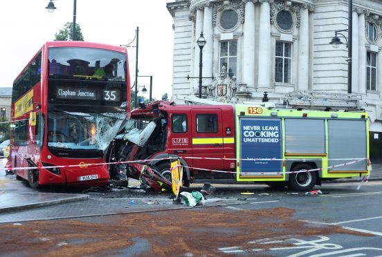 A view of the scene following a collision involving a bus, fire engine and car