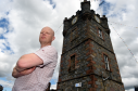 Dufftown business owner Alistair Jeffs next to the clock tower in the town, which will be dwarfed by the proposed electric poles.