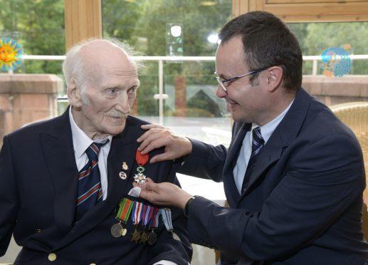 French Consul General Emmanuel Cocher presents the Légion d'honneur to Alex MacLachlan