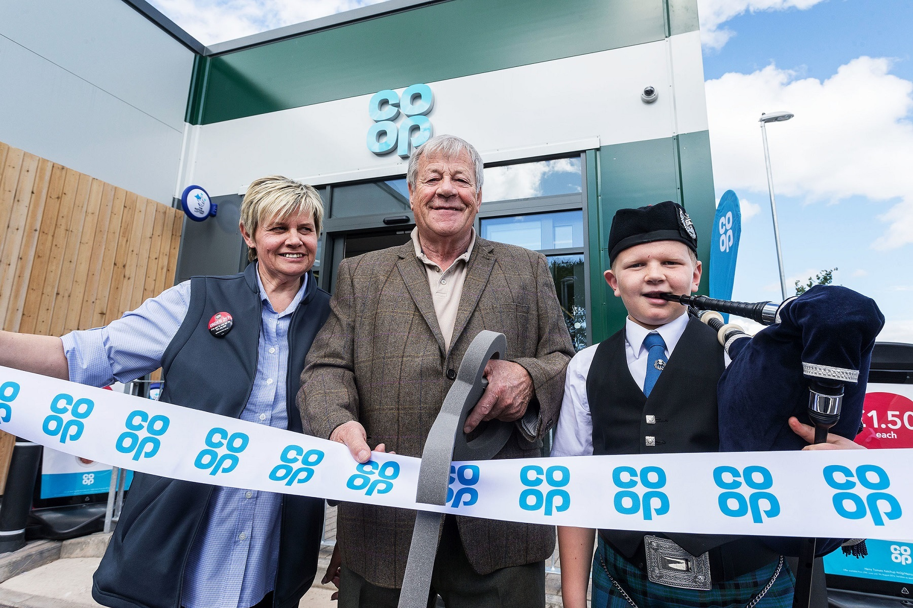 Store manager Sharon Cossans, local historian Fred Stewart and young piper, Tain Robbie, from Newtonhill Pipe Band cut the ribbon at the new Co-op store in Leathan Fields.