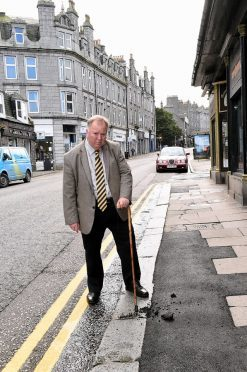 Councillor Bill Cormie who is angry at the council replacing broken and cracked slabs with bitmac on Rosemount Place.