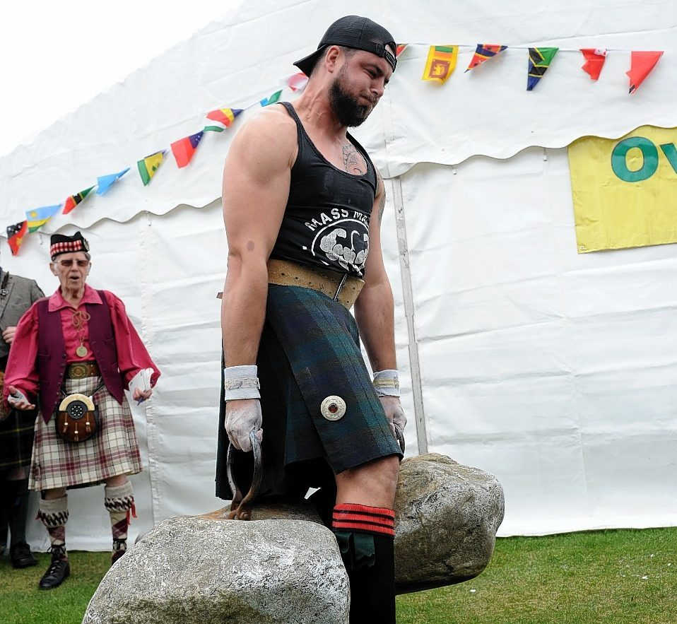 James Gardner takes on the mighty Dinnie Steens at Aboyne Highland Games yesterday. Credit: Kenny Elrick.