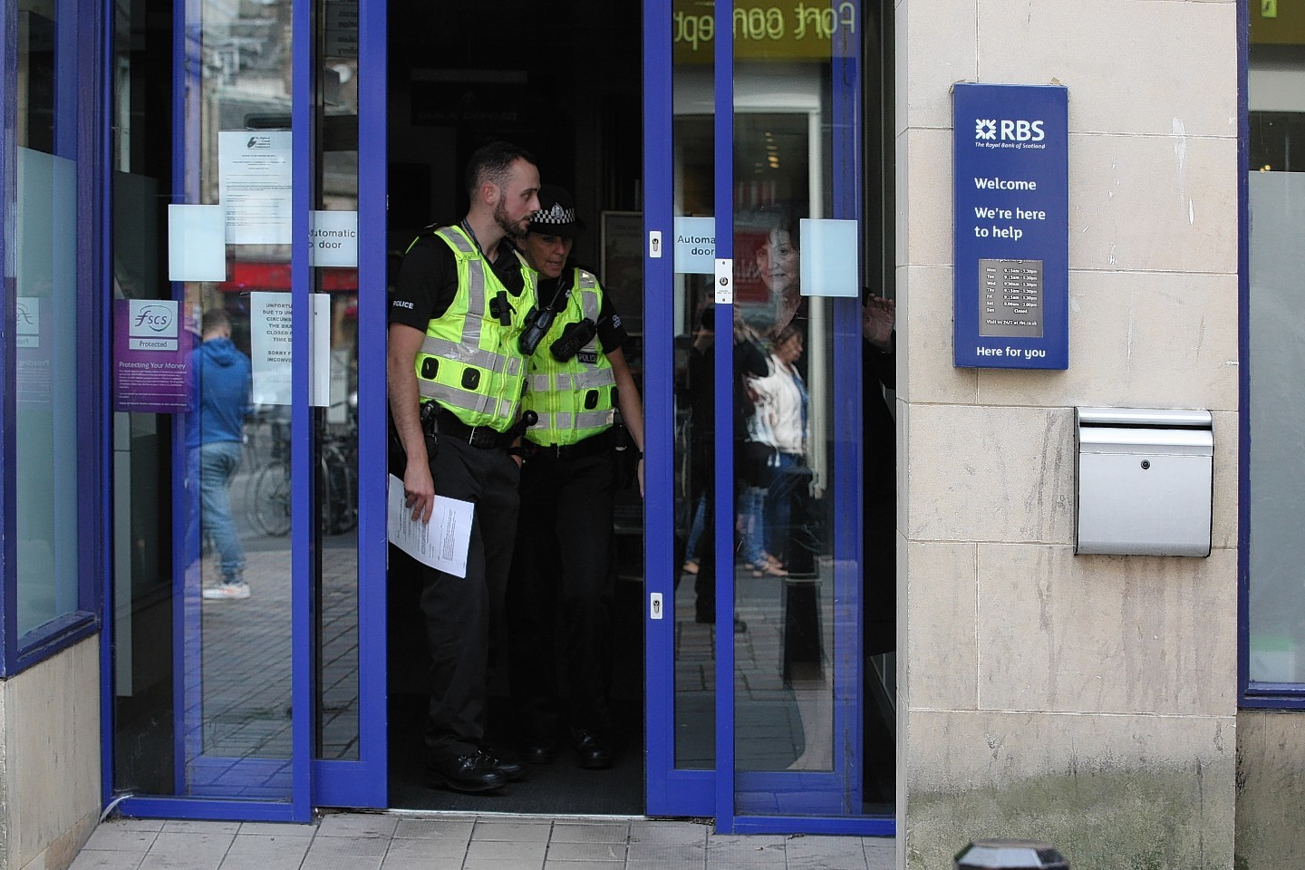 Police at the scene after the bag snatch in RBS, Inverness