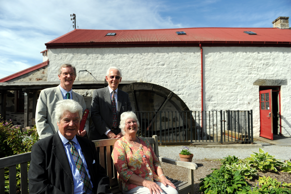 Knockando Woolmill, Aberlour, which won the European Union Prize for Cultural Heritage. Front L-R: Lord Cameron of Lochbroom and Dr Jana Hutt. Back L-R: Tom Duff and Dr Peter Collins, in front of the working water wheel. Picture by Gordon Lennox