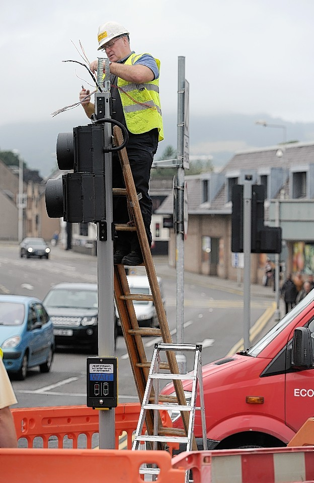 A Highland Council engineer repairs and replaces the damaged lights at the Huntly Street-Ness Bridge junction in Inverness.