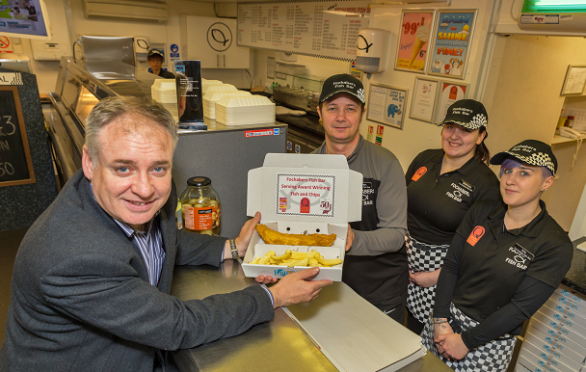 Darren Boothroyd serving MSP Richard Lochead a fish supper with Gemma McBean and Isla Cruickshank