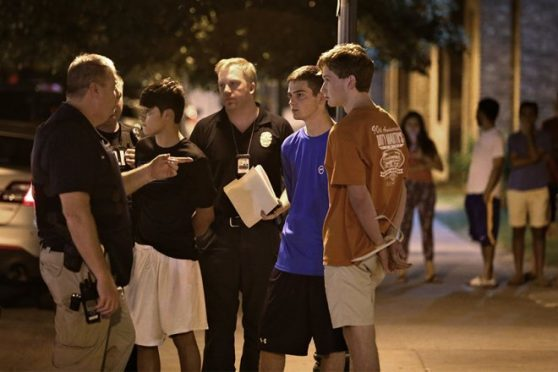 Daniel Hamilton Magee, in blue, stands with Austin Police Department officers after being arrested. Photo Credit: Daulton Venglar