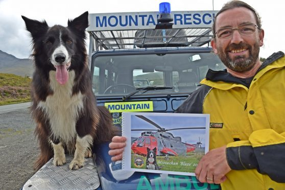 Blaze with his new calendar and Skye Mountain Rescue Team member Stuart Ashton