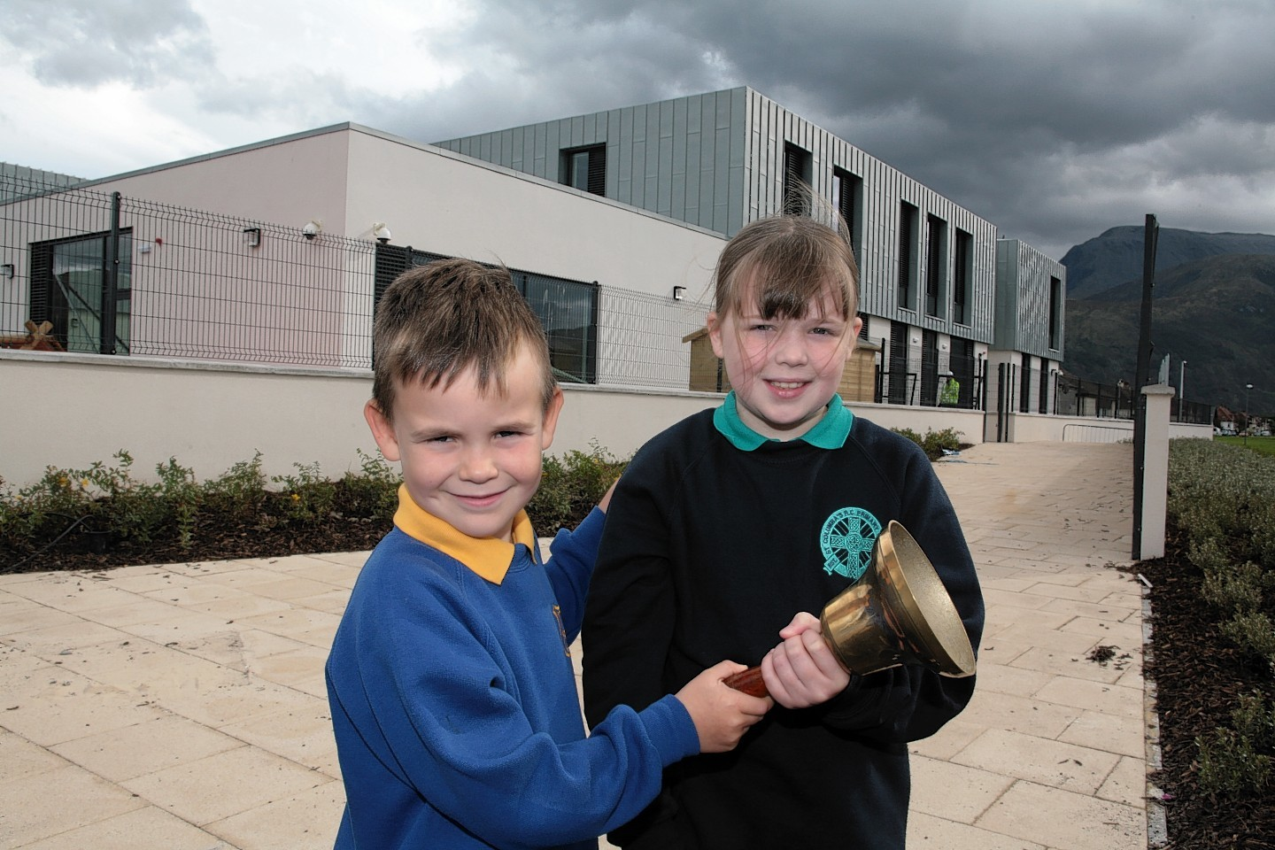 Coby Fyfe (left) of Caol Primary School and Emma McPhail of Lochyside Primary School ring the changes as both their schools close ready for the move into the new school behind them