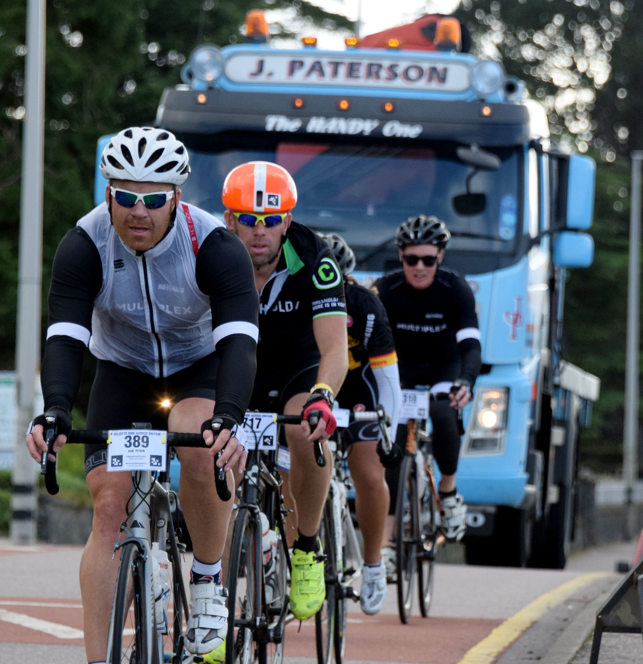 A large truck waits to pass a group of cyclists on the crowded A82 at Fort William
