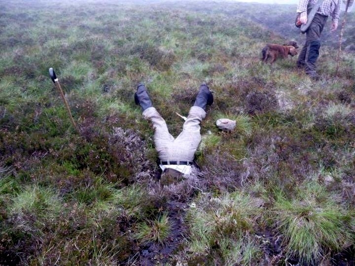 Gamekeeper Jonny Stevenson with head down hole. See Centre Press story CPHOLE; These dramatic pictures show a brave gamekeeper climbing head first into an underground pipe to rescue a dog who went missing on an Angus moor. Cocker spaniel Jazz disappeared while picking up game during a grouse shoot at the Invermark Estate on Tuesday. She was eventually found down a muddy open pipe on the moor. Gamekeepers dug through 6ft of wet peat to retrieve her Jonny Stevenson pushed himself down the pipe to check on the spaniel's condition.