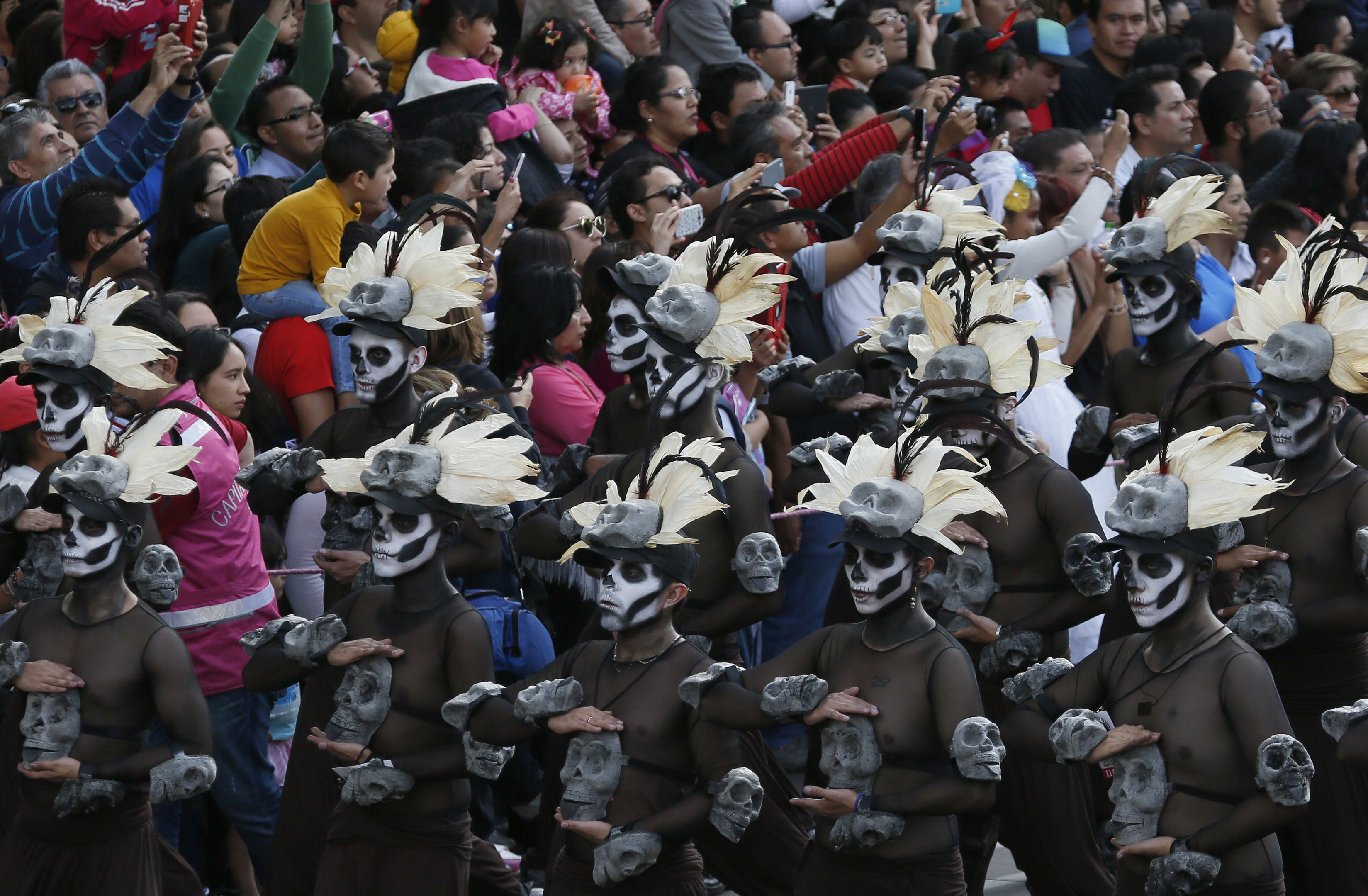 People watch the city's first Day of the Dead parade on Reforma Avenue in Mexico City,